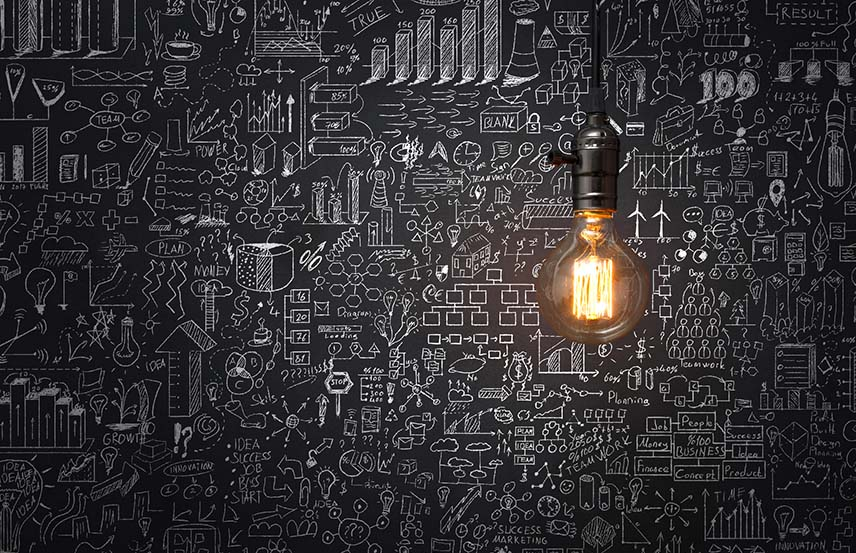 Lightbulb in front of chalkboard with doodles on it