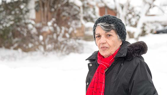 Older woman outside in the snow, wearing hat, scarf, and winter coat