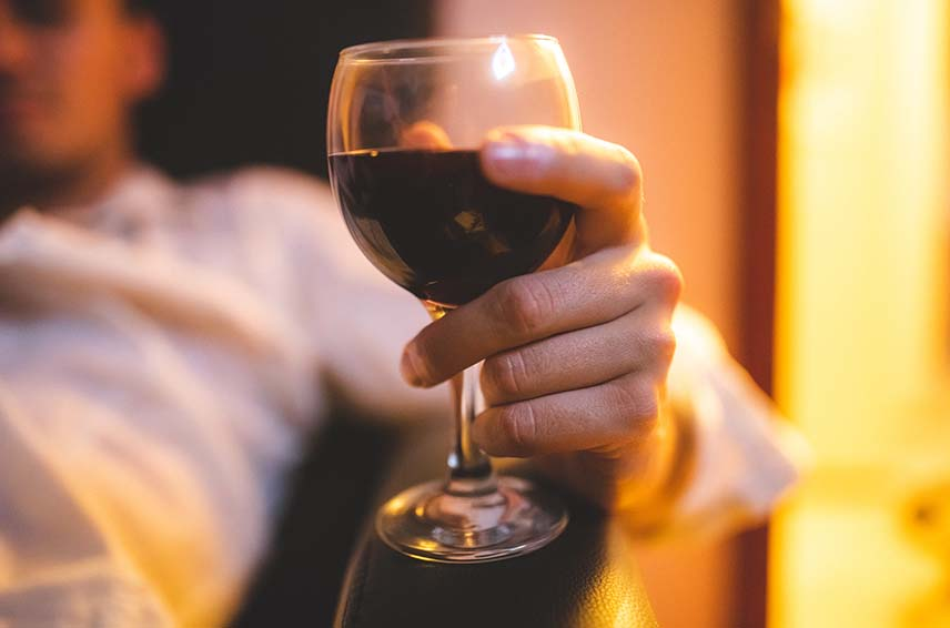 Close up of a person holding a wine glass