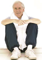 older man in exercise clothes with a towel sitting on floor