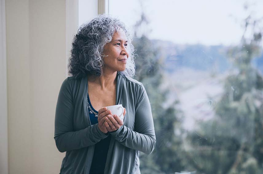older woman looking out the window and holding a tea cup