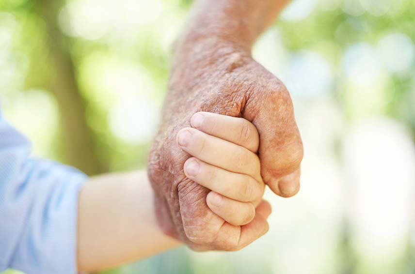 close up of an older person and younger person holding hands