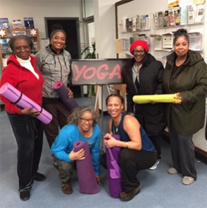 older adults with yoga mats in a library