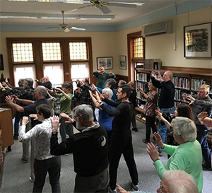Older adults do a group fitness class at a library