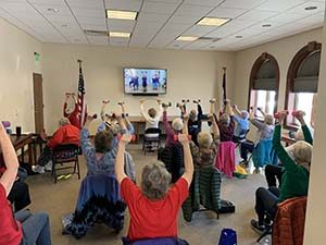 Older adults exercise to a fitness D V D in a library