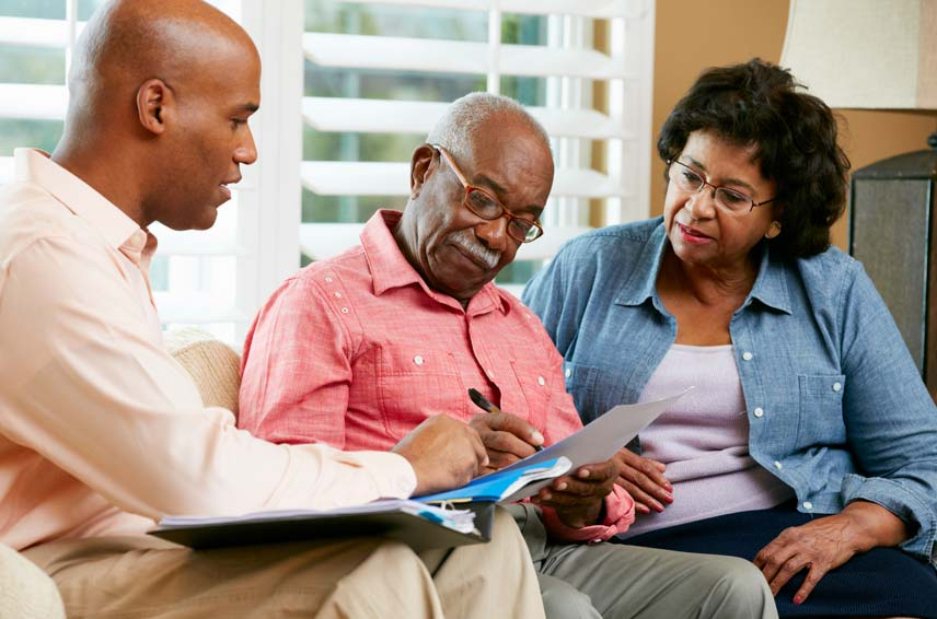older couple with younger man looking at paperwork