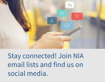 Woman looking at phone with social icons floating above. Text reads, Stay connected! Join NIA email lists and find us on social media