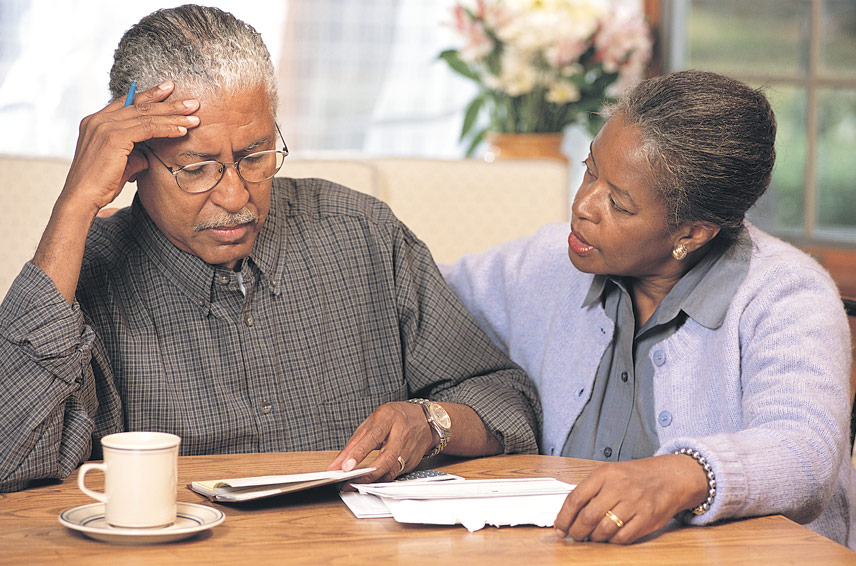 man and woman sitting around table while man views fact sheet
