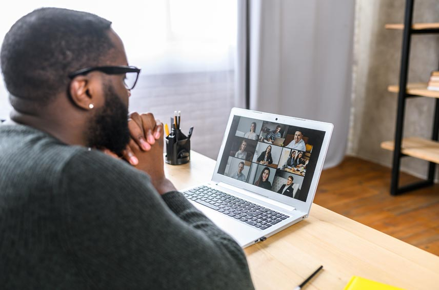 Man holding hands together while looking at laptop screen with other people displayed through webcam
