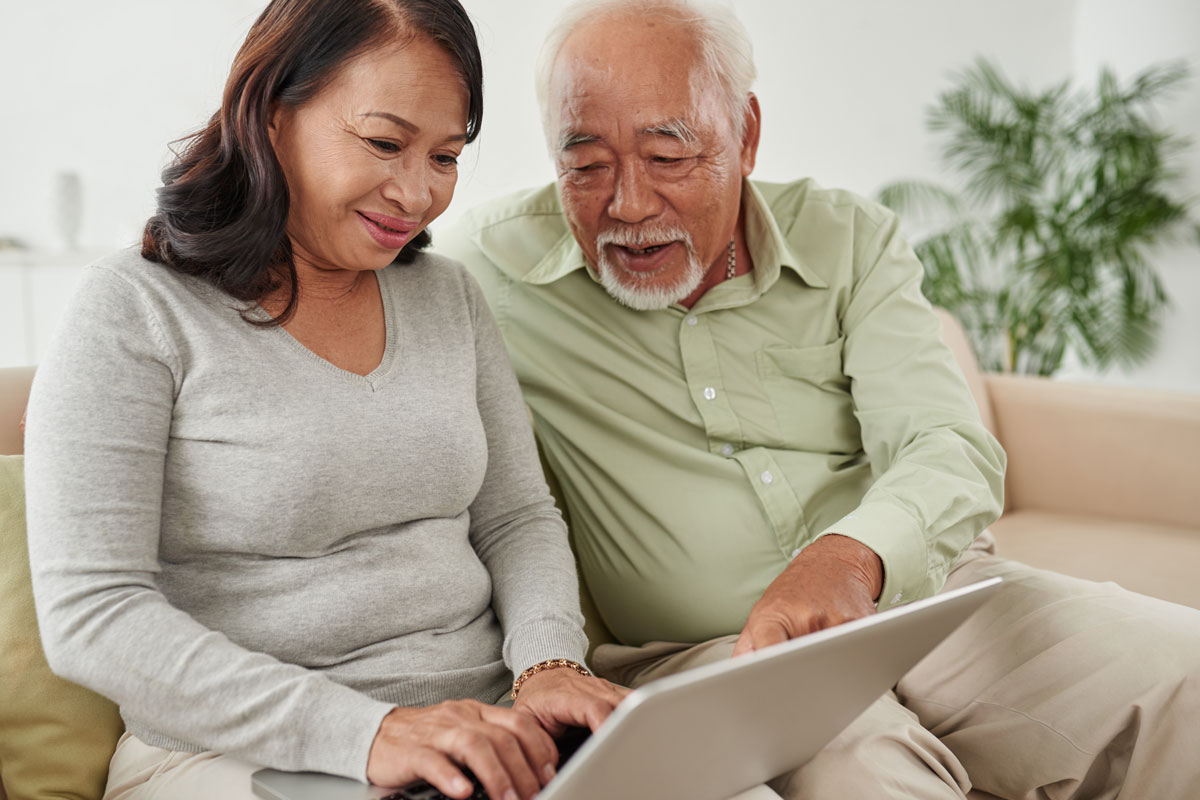 Older couple searching for Alzheimer's and related dementia trials on a laptop