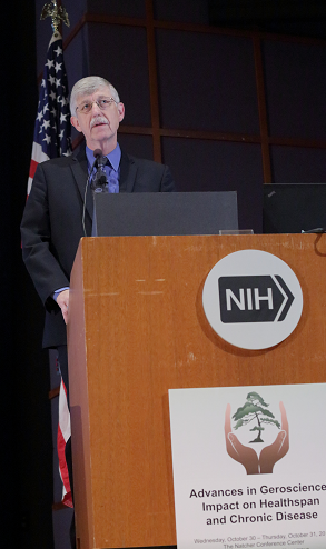 "Dr. Francis S. Collins, MD, Ph.D, director of the National Institutes of Health, opens the Geroscience Summit. Here, Dr. Collins stands at a podium with a flag behind. SIgns on the podium read ""NIH"" and ""Advances in Geroscience: Impact on Healthspan and Chronic Disease."""