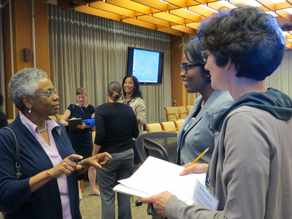 In the foreground, Dr. Marie A. Bernard speaks with two women. Across the room, a group of Scholars and NIH staff are visible having another conversation. Conference room seats, tables, and projection screens are visible.