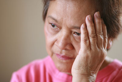 Older Asian woman looking concerned holding her hand to the side of her face.