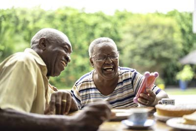 Older couple sitting at a table laughing and looking at a smart phone.
