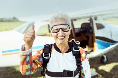 An older woman wearing goggles and a parachute standing in front of a small airplane.
