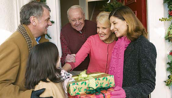 Older adults greeting family at the door with gifts