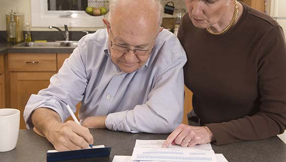 Man with Alzheimer's writing checks while caregiver supervises