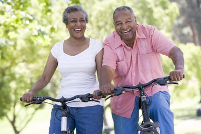 Older couple riding bicycles in a park.