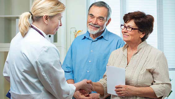 Female doctor talking to an older couple about lewy body dementia