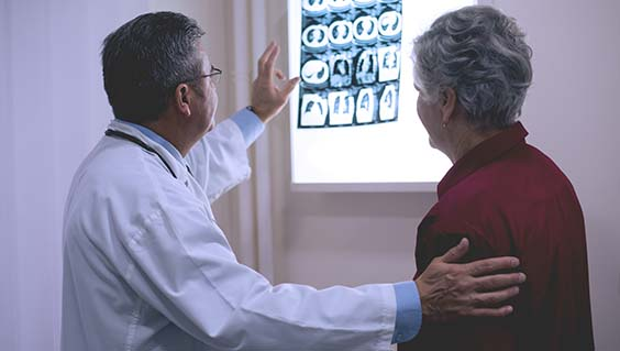 Doctor and patient looking at brain and body scans