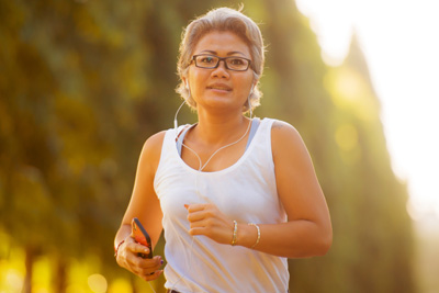 Middled-aged woman jogging outside, wearing ear buds