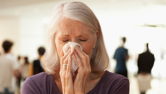 older woman with the flu blowing her nose