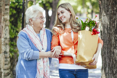 Older adult woman walking home from the grocery store with her granddaughter.