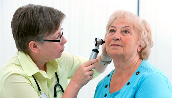 Nurse giving older woman an ear exam