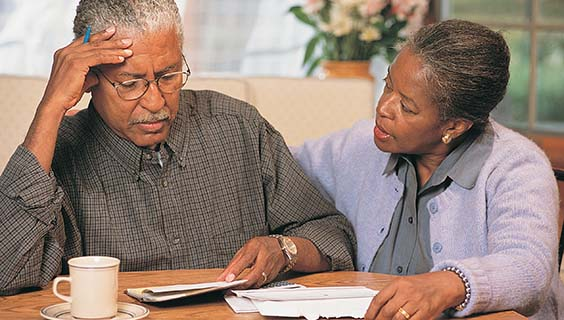 Older couple filling out legal and financial paperwork for people with Alzheimer's disease
