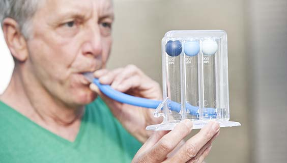 Older man testing his lung function