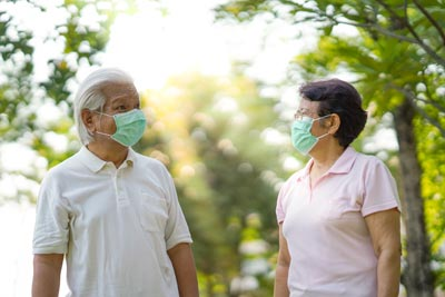 Older man and woman standing outside wearing surgical masks