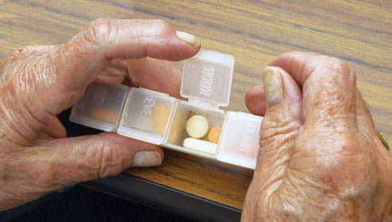 Older hands holding a pill box