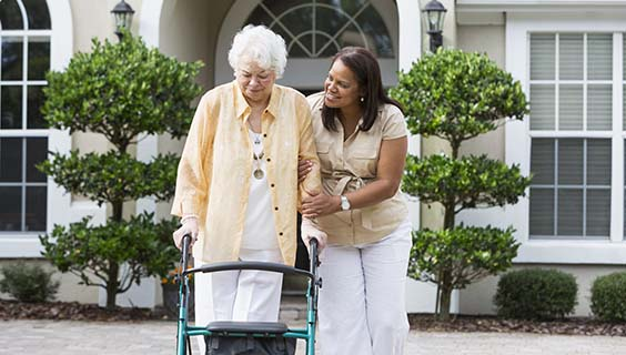 older woman using a walker with a caregiver's help