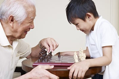 Older man playing chess with a young boy