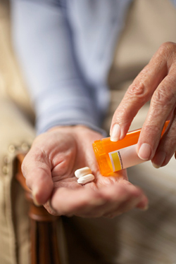 Older adult's hands with rx pills that sometimes may interact with pain medications.