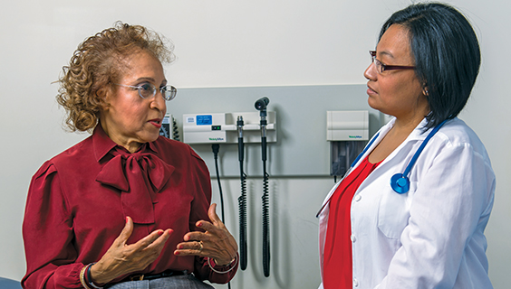 Older woman talking to her doctor about pain