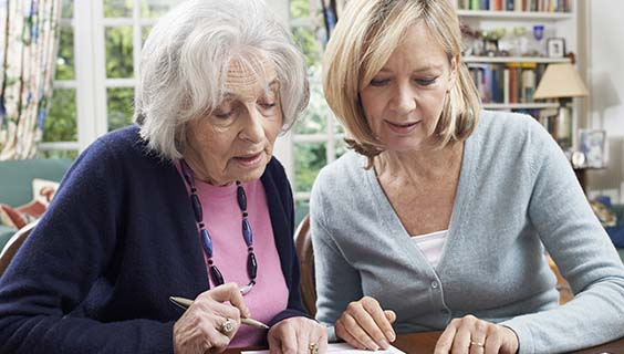 Older woman and her daughter going over long term care  finances