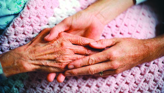 2 people holding hands on a pink blanket