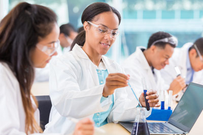 Black female scientist uses a pipette to drop liquid into a beaker, while her assistant is watching and recording the findings on a laptop.