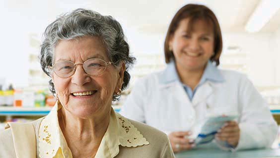 older woman at a pharmacy with pharmacist behind her