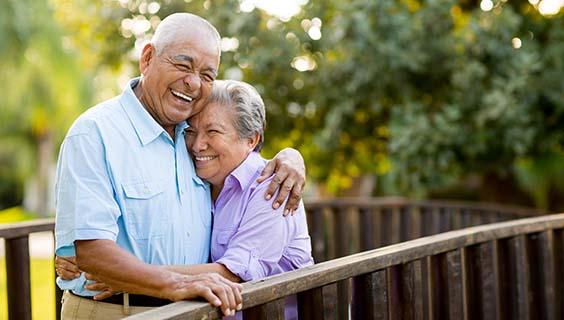 Pareja de ancianos riendo se abrazan en un puente