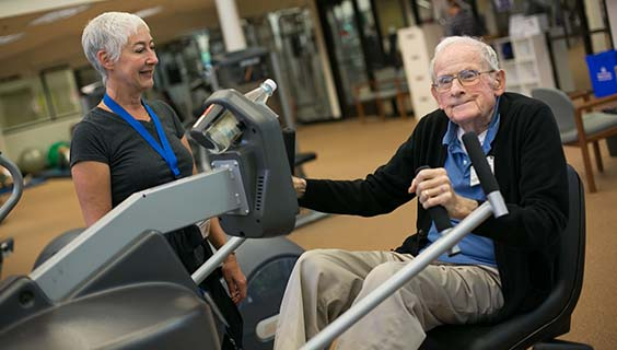 Older man on exercise equipment with a trainer