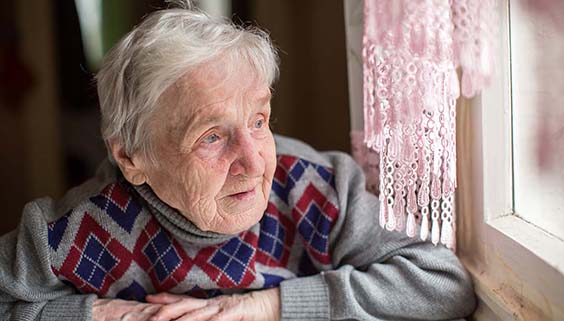 Older woman with Alzheimer's looking out of a window