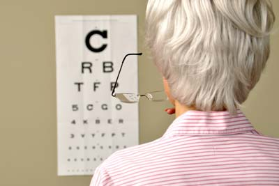 Older woman, holding her glasses, and standing in front of a traditional eye chart that appears blurry