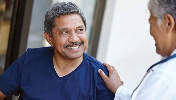 Hispanic man smiling at a doctor