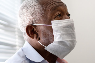 older adult with dementia, wearing a mask and waiting in doctor's office.