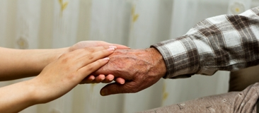 Younger hands holding an older person's hand