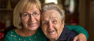 Older woman caring for her mother who has Alzheimer's disease