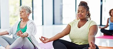 2 Women meditating in a yoga class