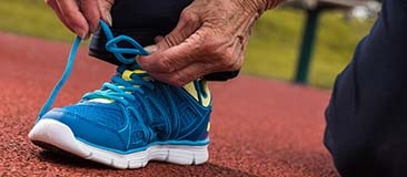 Close up of older person tying a running shoe